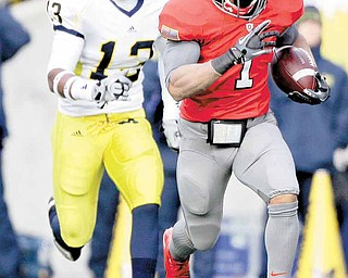 Ohio State running back Dan Herron (1) runs away from Michigan safety Carvin Johnson (13) during third quarter action in an NCAA college football game on Saturday, Nov. 27, 2010, in Columbus, Ohio. Herron finished the game with 175 yards and a touchdown on 22 carries on the Buckeyes 37-7 win.