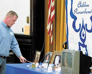 Lighting of a candle in honor of military personnel during a candle light vigil organized by the Bereaved Parents of the USA's Mahoning County Youngstown Chapter at the First Presbyterian Church Tuesday evening.