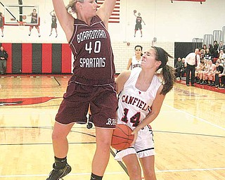 BASKETBALL - (14) Allie Pavlansky of Canfield drives to the hoop as (40) Kayleigh Lipke of Boardman plays defense during their game Wednesday night.