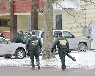 Law-enforcement officials approach a vacant house on Southern Boulevard they used as a training location and to show police presence in the neighborhood on Youngstown's South Side.