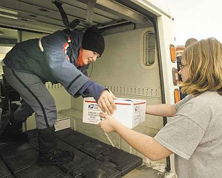 Campbell Middle School student Alyssa Gavlek, right,  hands a care package to postal worker Sue Hamilton.