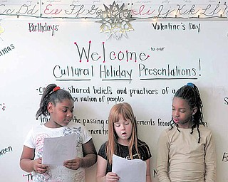 Third grade students (from left to right )  Jasmine Telfair Raelynn Haefke and Keriah Johnson present their favorite holiday to the class: Christmas. Third grade students of Woodside Elementary school invited family to join them Friday morning for a presentation of holidays from around the world and across the calendar.