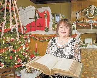 Carol Perkins stands amidst Christmas Decorations at The Rescue Mission in Youngstown on Tuesday afternoon.