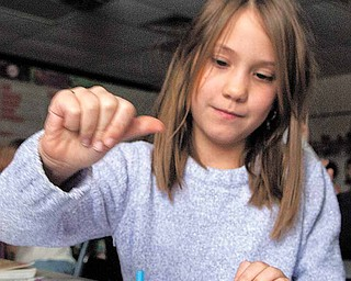 Jackson-Milton Elementary students Raenah Rader, 8, and Dalton Lockner, 9, play with a dreidel as part of an educational presentation on the history and customs of the Jewish holiday Hanukkah.