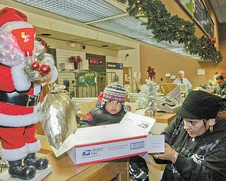 Maria Ruiz and her son Angel, 1, both of Youngstown, prepare to mail a package at theYoungstown Post Office Monday. Monday was one of the busiest postal days of the year.