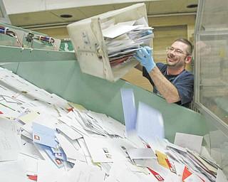 Youngstown Post Office employee Carl Flesher dumps a bind of mail onto a conveyor belt.