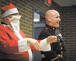 Steve Gasior, an eighth-grade science teacher, donned at Santa suit Monday as part of the Toys for Tots talent show at Choffin Career and Technical Center. Sgt. Robert Eggleston of the Marines took in the show with Santa. The talent show was a fundraiser for Toys for Tots and raised $900 for the cause.