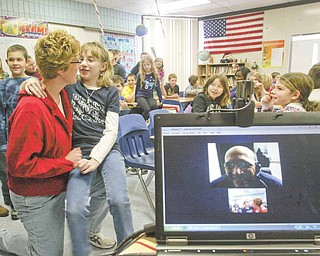 Geoff Clark, a U.S. Air Force Reservist speaks, to his daughter Kayla Clark and wife Kim Clark, at left, Monday using Skype, a program that allows users to chat online through video. Clark also answered questions from fourth-graders at Jackson-Milton Elementary during his digital visit.