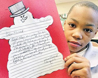 Taft Elementary fourth grader Jaiquale Gibbs displays the letter that he wrote to military service people in Afghanistan. The letters were a writing project in his class. Jaiquale wrote that his class would pray for the service people and that he wants to join the military.