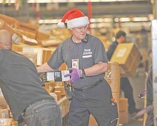 FedEx team leader Mike Almon, in Santa hat, sorts packages Monday with fellow employee Jason Taylor Monday, Dec. 13, 2010 in Anchorage, Alaska. Monday is expected to be the busiest day in FedEx history, with nearly 16 million packages moving on its conveyer belts, trucks and planes. That's up 13 percent from 14.2 million on the busiest day last year, and double what the company handles on a normal day. That jump in shipments bodes well for the nation's retailers, online stores and larger rival UPS, which has its single busiest day next week.