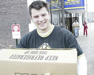 Brad Yaskowitz, an employee of Buffalo Wild Wings restaurant in downtown Youngstown, hauls eggs donated by his employer and Save-A-Lot stores to needy families. The restaurant here and in Niles passed out food Wednesday in Mahoning and Trumbull counties.