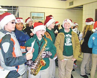 Making a joyful noise: Members of the Builders Club at St. Patrick School in Hubbard spread holiday cheer as they sang carols while walking from the school on Dec. 17 to Hubbard Manor, where they were greeted by residents of the manor. As one student played a saxophone the group sang as they walked through the halls and left a holiday gift at each apartment door. The caroling and gift-giving have been a tradition of the Builders Club for more than 10 years.