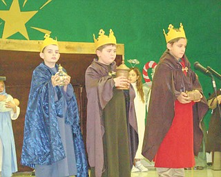 The gift of Christmas: The three kings, who took gifts of gold, frankincense and myrrh to the manger after the birth of Jesus, are portrayed by, from left, Cooper Muccio, Jeffery Hazy and Nick Matisi as the third-grade class of Joan Matune and second-grade class of Mellony Leonard recreated the story of the first Christmas for family and friends on Dec. 20 at St. Patrick School in Hubbard. This is the first year the classes undertook such an important project. The youngsters began practicing their roles in October.