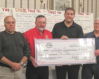 Supporting the foundation: On Dec. 12 the Valley Cruzers Car Club presented a check for $2,000 to the Touched by Nathan Foundation, formed by Kenneth and Vicki Pavalko in memory of their son. The car club has donated more than $14,000 to the foundation in the past four years. Participating in the check passing event during a meeting at A La Cart Catering in Canfield, were, from left, Frank Imburgia, club vice president; Steve Bendel Sr., president; Pavalko, who accepted the funds on behalf of the foundation; and Bob Brown, treasurer. Club members, not pictured, are Steve Goricki, Harry Barber, Gary Monroe and their wives. Club meetings are on Saturdays during warm weather at Chili's restaurant outside the Southern Park Mall. For more information on the club or to make a donation to the foundation, call 330-757-8324.