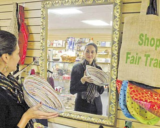 Yasmin Flor, manager of the Villa Shoppe in Villa Maria Community Center, holds a bowl made in Vietnam. The shop sells Fair Trade handcrafted items from Peru, Haiti, Bolivia, Mexico, El Salvador, Bangladesh, Philippines, India, Guatemala and Africa, as well as the United States.