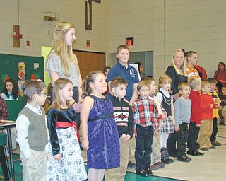 """A lighthearted holiday song: Backed up by students from the eighth-grade class at St. Patrick School in Hubbard, who provided their own version of the holiday classics, this group of kindergarten students entertained family and friends on Dec. 16 with their lively rendition of the holiday song """"Rudolph the Red Nosed Reindeer."""" The song was one of those featured as students from various classes took part in an annual program, """"A Christmas Spelling Bee,"""" written and directed by Mrs. Joan Deramo, music teacher, who was presented with a Christmas arrangement in recognition of her hard work."""