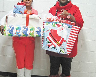 If you wish upon a star: The YWCA's Wish Upon a Star gift-giving project, in partnership with community groups and individuals, collected new toys, books and games that were distributed to more than 80 homeless and low-income children in the YWCA housing program. Holding an armful of gifts she received for her five children is, at left, Lillian Peoples, who has a disability that prevents her from working. Residents in the Transitional Housing Program at the YWCA, her family is one of the 41 families helped through the Wish Upon  a Star project. Carrying some of the gifts for Peoples is Vicki Winphrie, YWCA living skills educator.