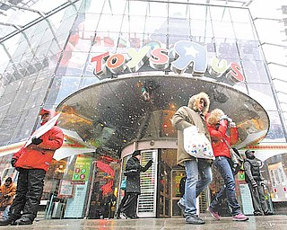 Shoppers leave the Toys R Us store in New York's Times Square, Sunday, Dec. 26, 2010.