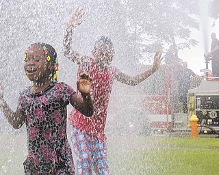 Janiyah Vogle, of Warren, and Andre Carter, 9 of Youngstown, enjoy cooling off with the help of Youngstown Fire Department's Engine 2 during the Annual African Cultural Weekend at Mill Creek Community Center on Saturday afternoon.