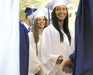 A Poland graduate with fist clenched walks past Lindsay Mitchell (left) and Katarina Meris (right) on his way to receive his diplomia holding a penny that he tried to drop into the principals palm during a handshake at Poland's 2010 Commencement Ceremony at the high school gymnasium on Sunday afternoon. Pennies could be heard hitting the floor throughout the ceremony as students backed out of the practical joke and the principal refused to accept the comical offering.