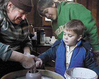 Vendor, Mary Bobersky (left), of Lake Milton, demonstrates how to shape pottery for her nephew, James Auden (back right), 11 also of Lake Milton, and Jackson Spin, (front right) 2 of Boardman, during the Millcreek Holiday event at Lanterman's Mill on Sunday afternoon.