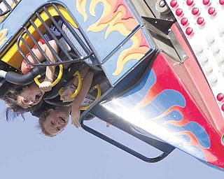 Carlie Chepke, 15, and Sarah Melfe, 14, both of Austintown, scream as they find themselves inverted on a fair ride that takes riders around in a loop  on Sunday afternoon.