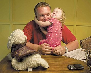 YSU Head Football Coach Eric Wolford, shares a moment with his daughter Marlee at the Wolford Home in Liberty on Thursday afternoon.