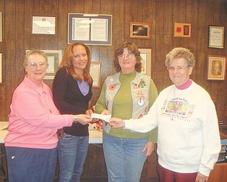 The spirit of giving: Sister Midge, Lisa Petro, Roberta Lawrentz of Girard Junior Women, and Sister Marjorie, from left to right, display a check that was presented to the Emmanuel Care Center in Girard. The check is from Girard Junior Women, who sponsor fundraisers that benefit the Girard community. GJW donates annually to the Emmanuel Care Center, which provides for the needy families of Girard. For Thanksgiving the group donated 400 bags of food and IGA gift certificates, and for Christmas they donated 600 presents. The center houses transitional families.