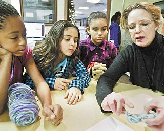 Shaniya Ray, 10 (left), and Yanessa Butler, 7 (center), and Yeleysa Butler, 10, all members of the Boys and Girls club of Youngstown, watch as Katherine Bair, tutorial and enrichment director for the club, demonstrates crocheting on Monday, Dec. 27.