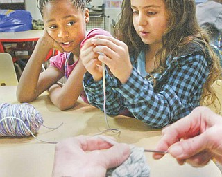 Shaniya Ray, 10, left, and Yanessa Butler, 7, both members of the Boys and Girls club of Youngstown, watch as Katherine Bair, tutorial and enrichment director for the club, demonstrates crocheting at the club Monday, Dec. 27.