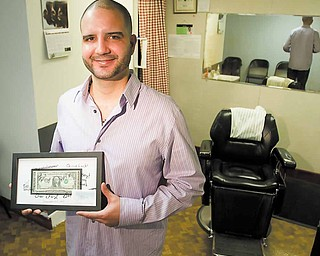 Holding the first dollar he made at his new job, Paul Gonzalez Jr., of Youngstown, stands in his barbershop on  the second floor of the Youngstown YMCA.