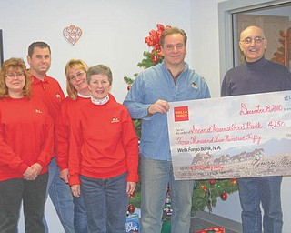 Making an investment: Wells Fargo Advisors made a sizeable investment in the community recently by providing a $4,250 grant to Second Harvest Food Bank of Mahoning Valley. The grant will help the food bank provide food for those in need in the Mahoning Valley. Wells Fargo & Co. has a strong legacy of giving to the community. In 2009 the combined company contributed more than $200 million in grants and sponsorships to nonprofit organizations and 1.4 million team-member hours volunteering in communities across the United States. Participating in the presentation of the grant to Second Harvest were, from left, Patti Wilson, David Patrick, Sandy Haynes and Beth Ortz, who watched as David Croutch, manager of the Canfield Branch of Wells Fargo Advisors, passed a facsimile of the check to Michael Iberis, executive director of the food bank.