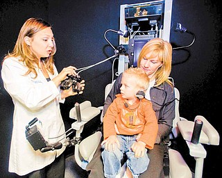 Dr. Cara Makuta, left, gets the goggles ready for Casey Ecker, 3, as he sits on the lap of his mother, Heidi Brandl, of Newport Beach, California, before being tested by Dr. Cara Makuta, in the Neuro Kinetics Rotational chair, which helps evaluate overall inner ear functions.