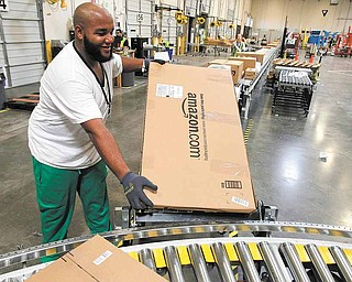 In this Nov. 11, 2010 photo, Leacroft Green places a package to the correct shipping area at an Amazon.com fulfillment center, in Goodyear, Ariz. Amazon.com, the source of many presents good, bad or ugly, has patented a system that would let people exchange unwanted gifts for those they want before anything is actually shipped. For now, though, it's just a patent, so until Amazon figures out how to implement it, you may be stuck with that itchy sweater from grandma.