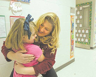 Struthers Elementary School Principal Maggie Kowach hugs first-grade Student Lauryn Mileto. The principal has formulated a list of strategies to encourage students to attend school regularly during Count Week - The period of time when students in a district are counted to determine funding for the district.