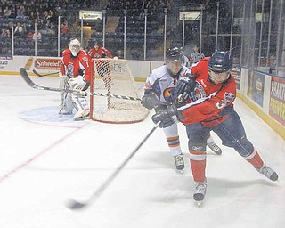 Conner Kucera of the Des Moines Buccaneers fights for possession of the puck against Phantom Ty Loney.