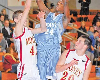Youngstown East's #24 Antonio Woods puts up a shot while Cardinal Mooney's #42 Doug Caputo and #20 Joe DeNiro get in front of him.