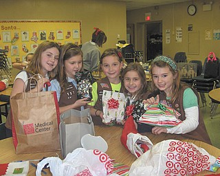 """Holiday wrap session: Girl Scout Brownie Troop 157 of Holy Family School in Poland members have """"adopted"""" children who live at the Beatitude House in Youngstown. In October the troop provided the youngsters with goodies, and in December they contributed small gifts and stuffed stockings for each of the children. Displaying some of the gifts they wrapped are, from left, Annie Daprile, Ava Szalay, Lucy Graziano, Anna Wollet and Lucia Naples."""