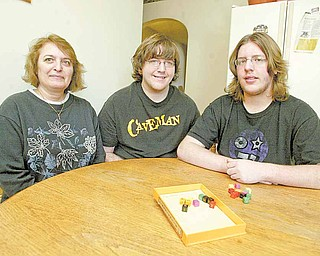 Travis Court, 15, right, qualified to go to a national Academic Games Leagues of America tournament this year. Pictured with him are his mother, Betsy Court, and his brother Josh, 20, at their Ellwood City, Pa., home.