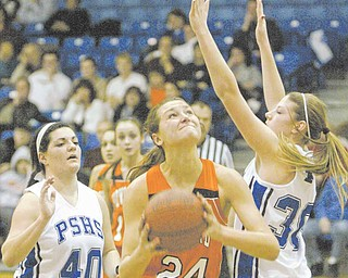 Howland's #24 Taylor Williams shoots through Poland's Allison Berend, left, and Maura Bobby during first-half action at Poland Monday.