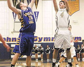 Gerrod Hrusovsky (4) shoots for two as Erik Baker (10) tries for the block during their game Tuesday night in Lowellville.