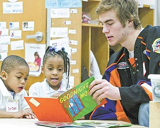 Youngstown Phantoms hockey player Matt O'Connor reads to Millcreek Children's Center students Jor'Den Young and Monica Cash, both 3, during a visit Thursday. Members of the team read to kids, distributed stuffed animals and presented a $500 check to the center from the BJ Alan Corp.