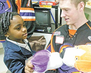 Unique Moore is shown here in this January 2011 photo with Youngstown Phantoms hockey player Adam Berkle. The 5-year-old died Monday in Akron Children's Hospital, Akron, where she was taken after being pulled Sunday afternoon from Willow Lake Park campground swimming pool in Champion Township in Trumbull County.