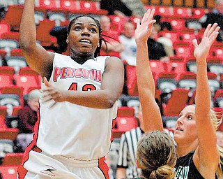 YSU Penguin Brandi Brown finds a hole between her defenders Adrian Ritchie (13) and Kayla Tetschlag of Green Bay and shoots.