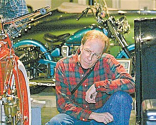 Randy Kretz of Newbury, Ohio, inspects a 1908 Crouch motorcycle at the Packard Museum on Saturday, January 8th.  This is the oldest motorcycle in the museum's Motorcycles on Main Street show.