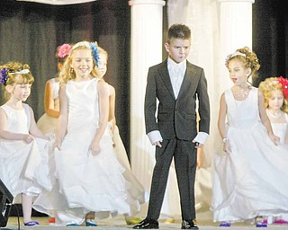 Christopher McMahan, 7, of Niles models a ring bearers Tuxedo while flower girls model dresses during Evaline's Bridal show Sunday at Covelli Center