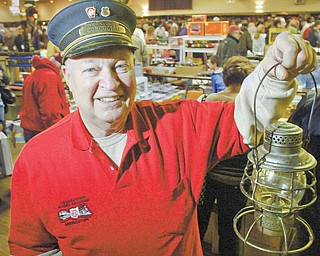 Jim Pope of Berlin Center, president of the Youngstown Model Railroad Association, holds a railroad lantern during model railroad flea market Sunday at McMenemys in Niles.
