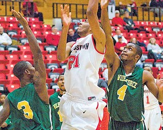YSU Penguin Zack Rebillot drives to the basket while being defended by Christopher Olafioye (3) and Yann Sani (4) of the Wilberforce Bulldogs.