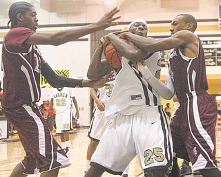 Warren Harding's Delshawn Bell (25) battles for the ball with Boardman's Leondre Jackson (23) and T.J. Irving (4) during their game Tuesday night.