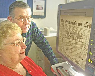 Dorothy Yakubec of Salem and DeWayne McCarty of Columbiana look at a microfilm of the Columbiana Ledger, a now defunct newspaper, at the Columbiana Public Library.